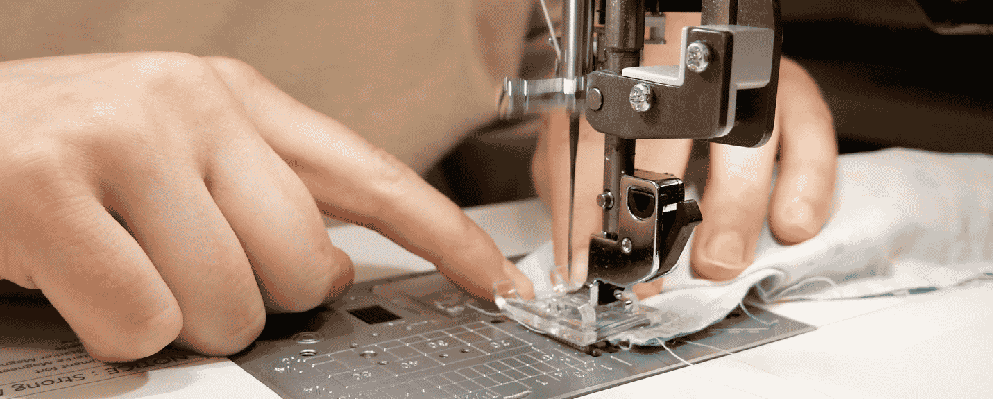 A picture containing sewing machine, person, appliance, indoor Description automatically generated